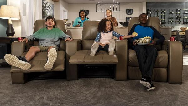 home theater seating - Families and friends enjoying TV on reclining home theater seating.