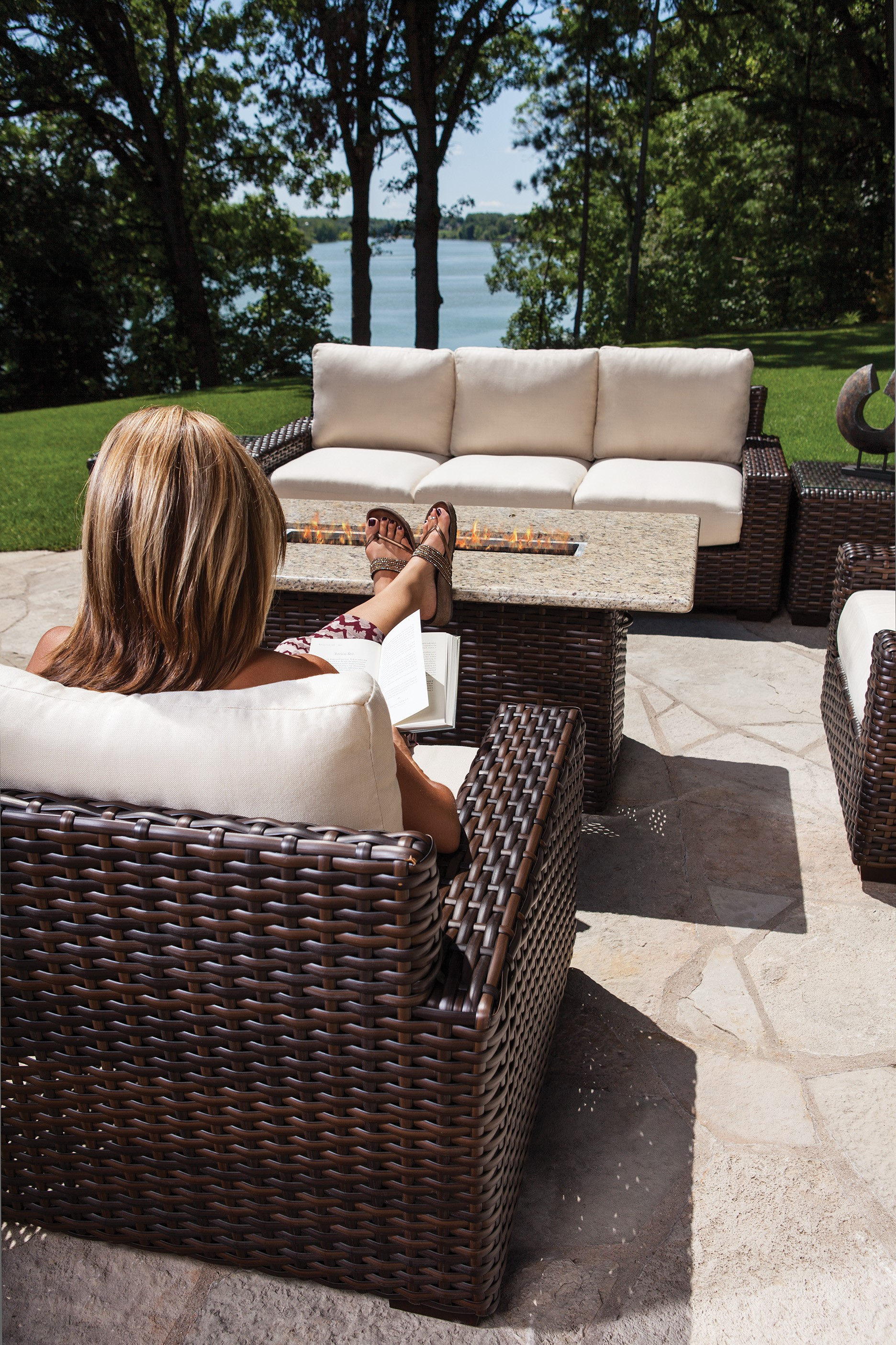 outdoor furniture outdoor living spaces - a woman sitting in a patio chair reading a book