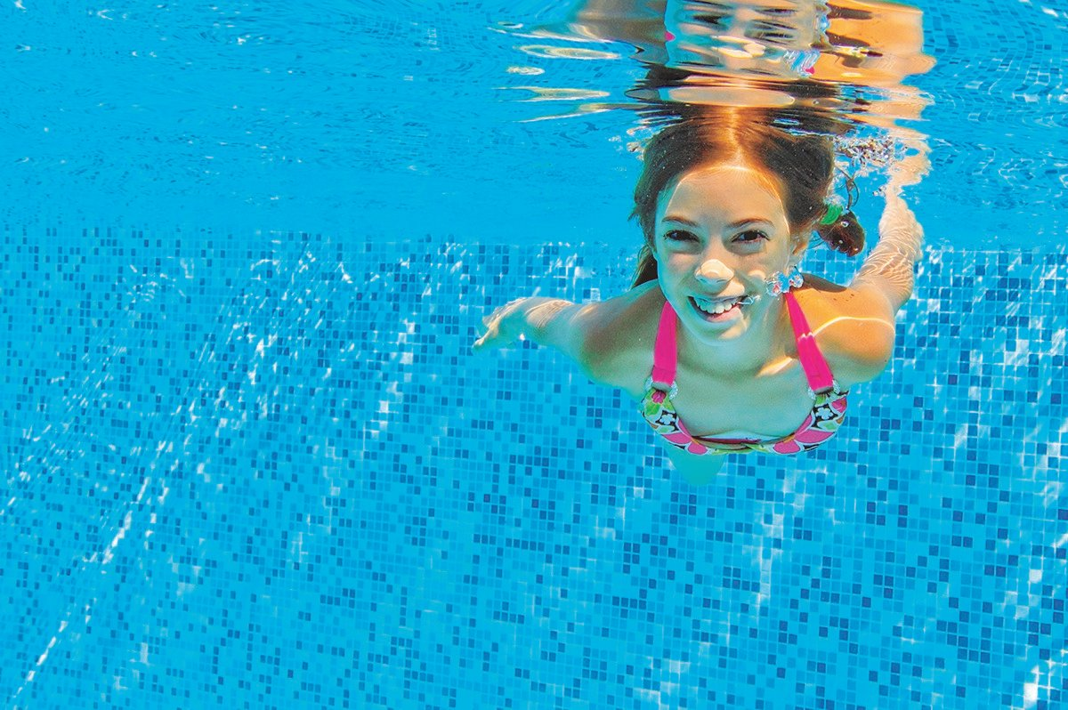 pool water test kit - how often should I test my pool water - young girl underwater in a clean pool